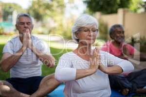 Senior people with closed eyes meditating in prayer position