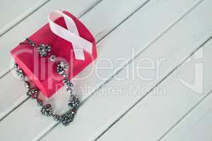 High angle view of jewelry with red box and pink Breast Cancer Awareness ribbon