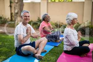 Smiling senior man meditating in prayer position with friends