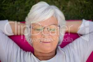 Senior woman resting with closed eyes on exercise mat