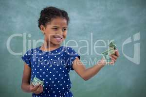 Smiling girl looking at paper currency