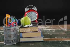 Alarm clock, apple and chalk on stack of books with pen holder
