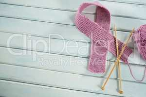 Overhead view of pink woolen Breast Cancer Awareness ribbon with crochet needles