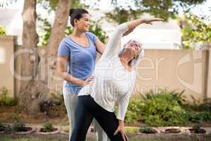 Smiling trainer instructing senior woman while exercising