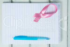 Overhead view of pink Breast Cancer Awareness ribbon and spiral notepad with pen