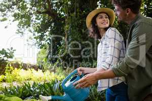 Romantic couple watering plants with watering can in garden