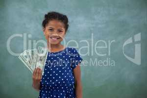 Portrait of girl showing paper currency