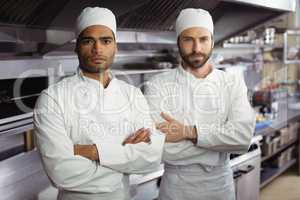 Portrait of two chefs standing together with arms crossed in commercial kitchen