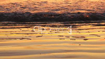 Reflection of sunset on the beach shore