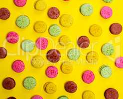 Colorful pastry macaroons on a yellow background