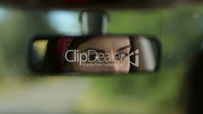 Reflection of cute woman in car rearview mirror