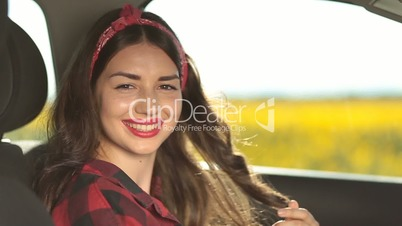 Pretty smiling female driver sitting in the car