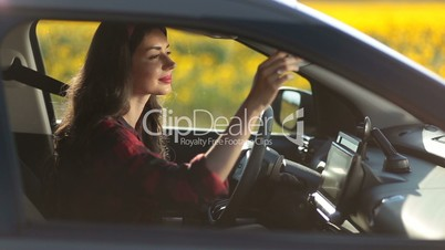Pretty young woman driving car on summer road trip