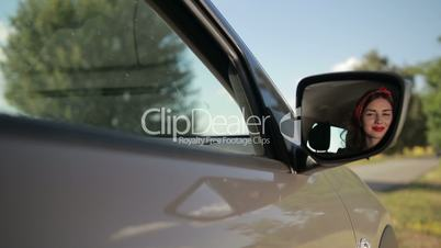 Reflection of cute girl in rearview mirror of car