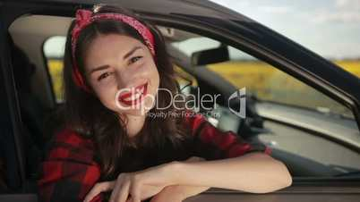 Stylish brunette woman leaning out of car window
