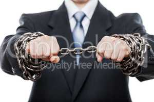 Businessman struggles metal chain tied hands