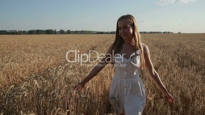 Pretty smiling woman relaxing in wheat field