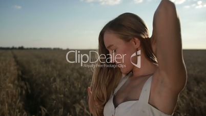 Adorable girl playing with hair in cereal field