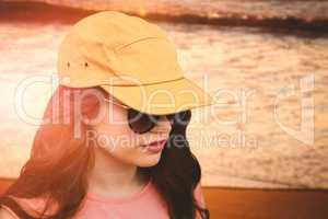 Composite image of beautiful female model wearing sunglasses and cap