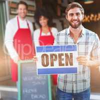 Composite image of portrait of male owner holding open sign