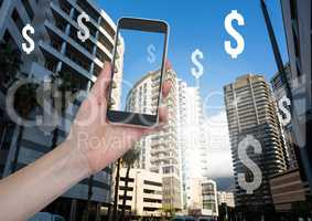 Holding phone and Dollar icons in financial district skyscrapers city