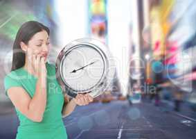 Woman holding clock in front of city rush