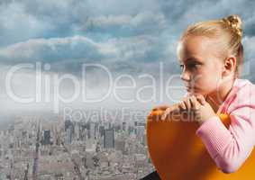 Girl sitting contemplative in chair over city