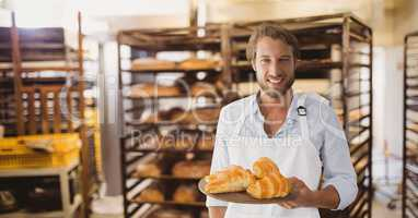 Happy small business owner man holding croissants