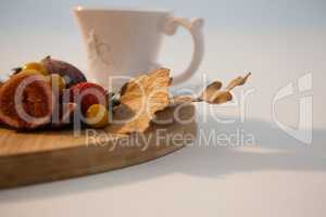 Autumn leaves, various fruits and cup of tea on chopping board
