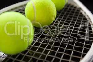 Close up of fluorescent yellow balls on tennis racket