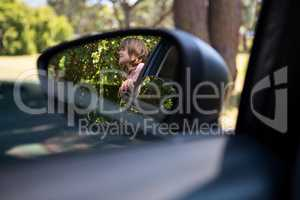Reflection of teenage girl in wing mirror standing beside a car