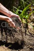 Woman pouring soil in garden