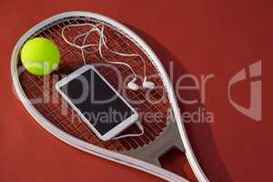 High angle view of mobile phone with in-ear headphones and ball on tennis racket