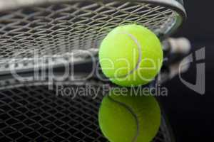 Close up of tennis racket on ball with reflection