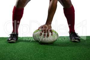 Low section of sportsman with rugby ball