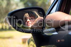 Reflection of teenage girl in wing mirror of a car