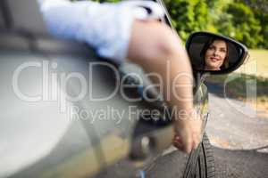 Reflection of woman in wing mirror driving a car