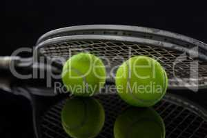Close up of fluorescent yellow tennis balls with racket