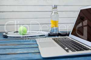 Close up of laptop by tennis racket and balls with water bottle against white wall