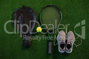 Directly above shot of racket with ball and sports shoes