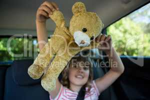Teenage girl playing with teddy bear in back seat of car