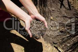 Woman holding soil in garden