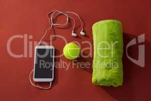 Overhead view of tennis ball amidst napkin and mobile phone with in-ear headphones