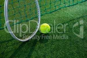High angle view of tennis ball with racket by net