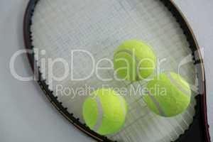 Close up of fluorescent yellow tennis ball on racket