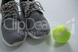 Close up of sports shoes with tennis ball