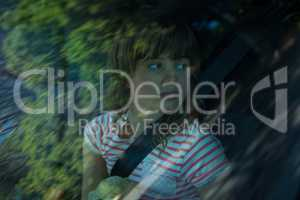 Teenage girl with teddy bear sitting in the back seat of car
