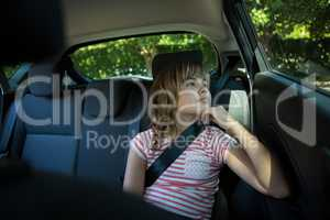 Teenage girl sitting in the back seat of car