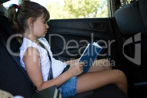 Teenage girl reading book in the back seat of car