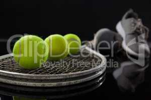 Close up of fluorescent yellow tennis balls on racket by sports shoes